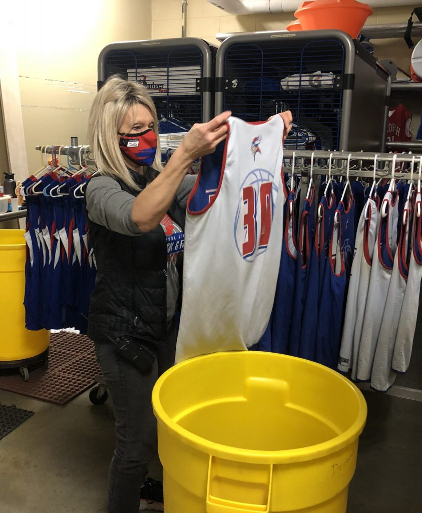 Custodian hanging up basketball uniforms