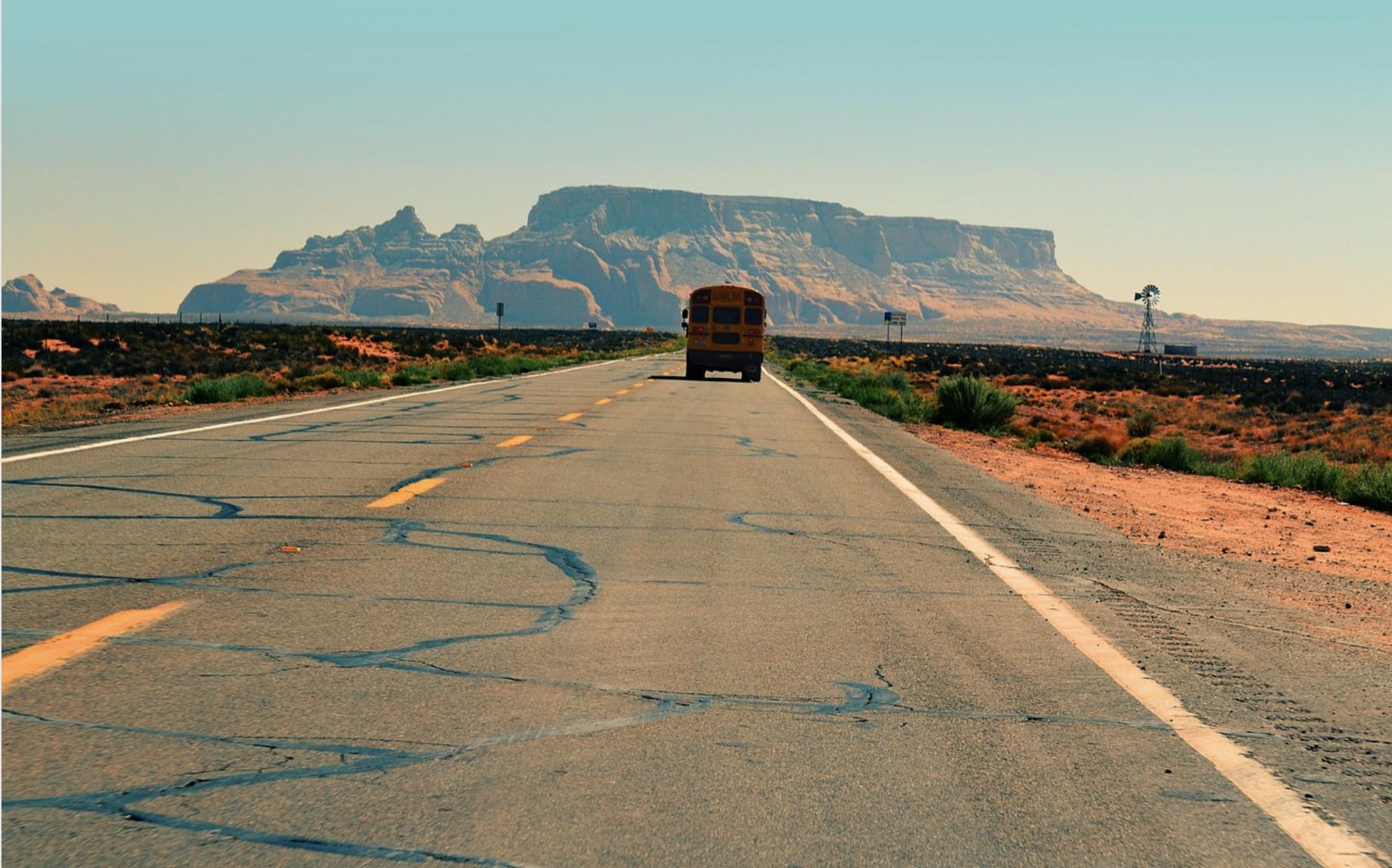 SCHOOL BUS DRIVING DOWN ROAD