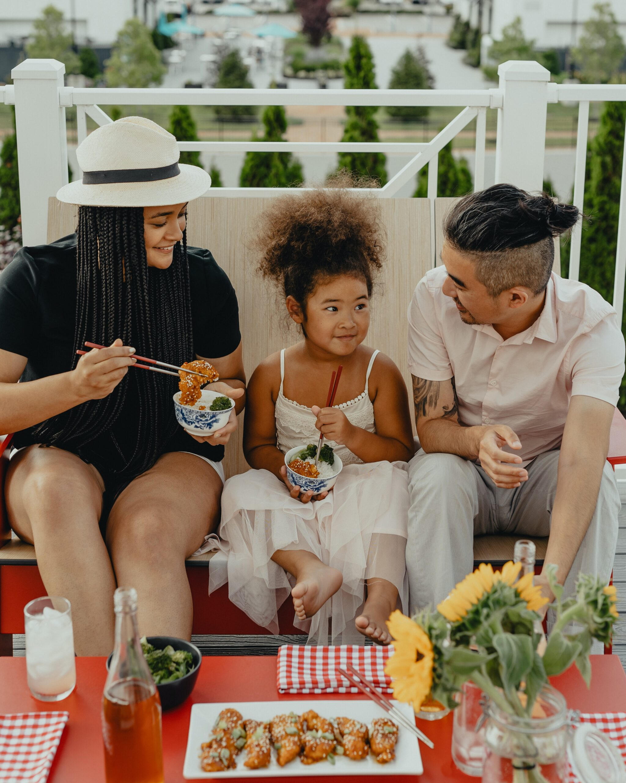 Man, woman, and child eating with chopsticks