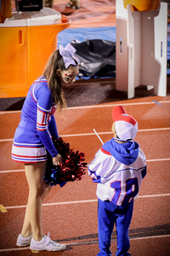Cheerleader talking with a fifth grade student