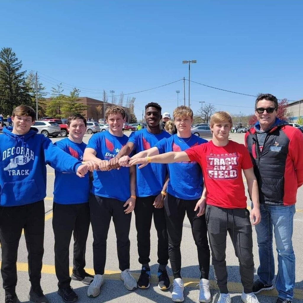 Boys track players with coach